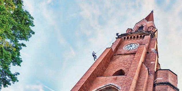 Mensch klettert an Kirche empor