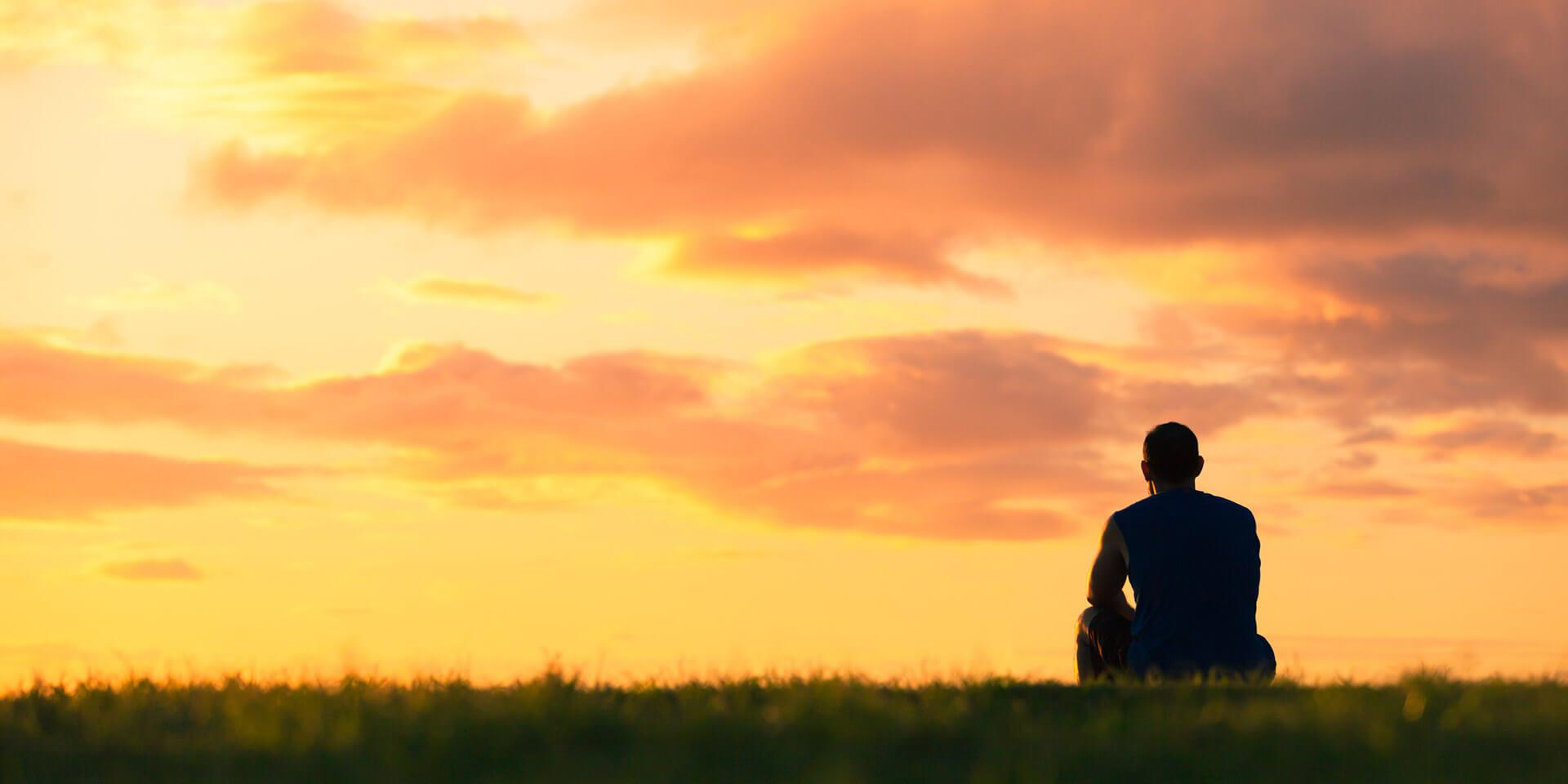 Mann blickt in den Sonnenuntergang