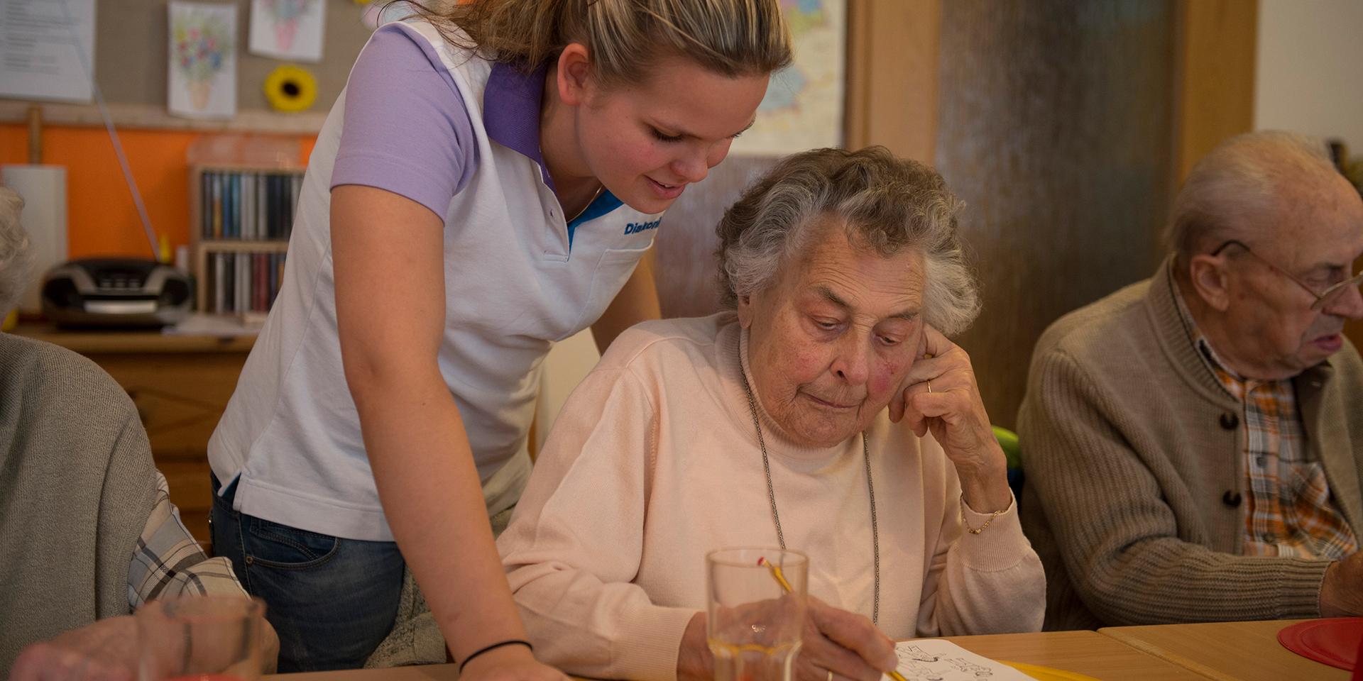Eine alte Frau und eine junge Mitarbeiterin der Diakonie