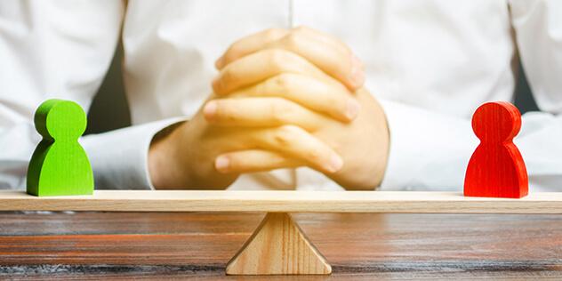 Ein Mann mit gefalteten Händen sitzt vor einer ausgeglichenen Waage., Bild: © iStockPhoto / Andrii Yalanskyi